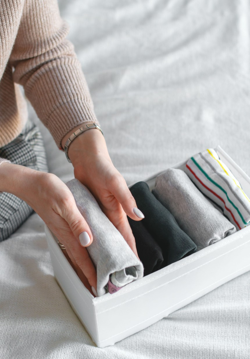 Frau stellt gefaltete T-shirts in eine Kiste, einfach aufgeräumt
