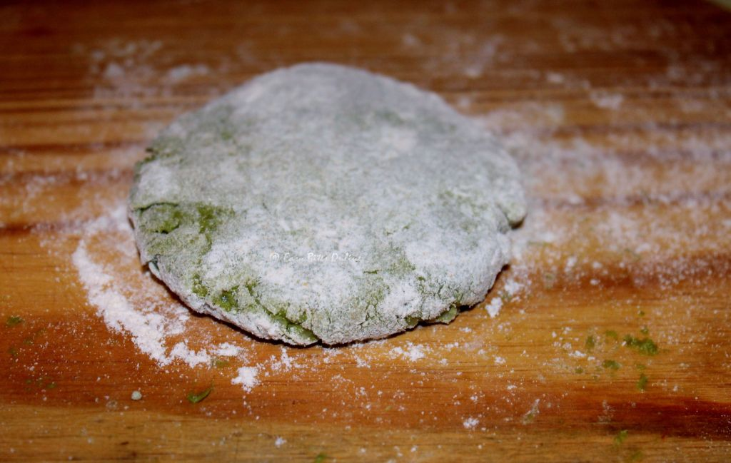 taking a small portion of the dough, make a smooth ball. flatten it to make a patty. dust it in flour