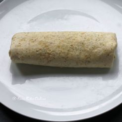 fold one side over tightly, fold in the edges, roll the covered wrap again tightly to form a nice burrito like this