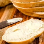 Butter spread on a slice of French Bread.