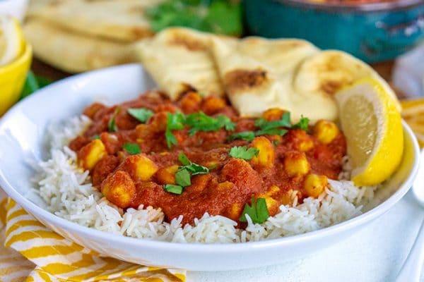 Chana Masala over rice on a white plate.