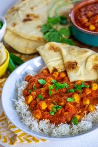 Overhead view of chana masala on a white plate with naan.
