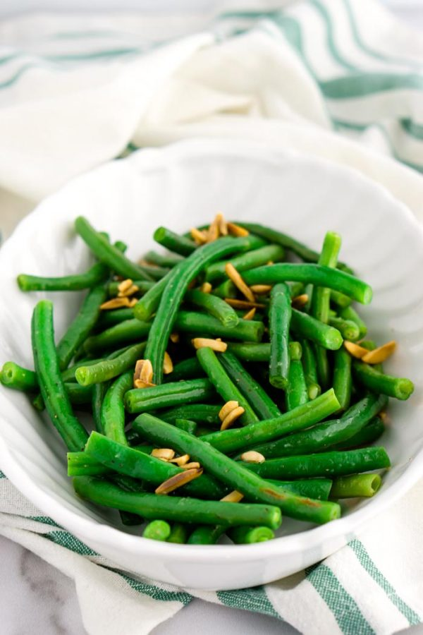 Finished Green Beans Almondine in a white serving bowl.