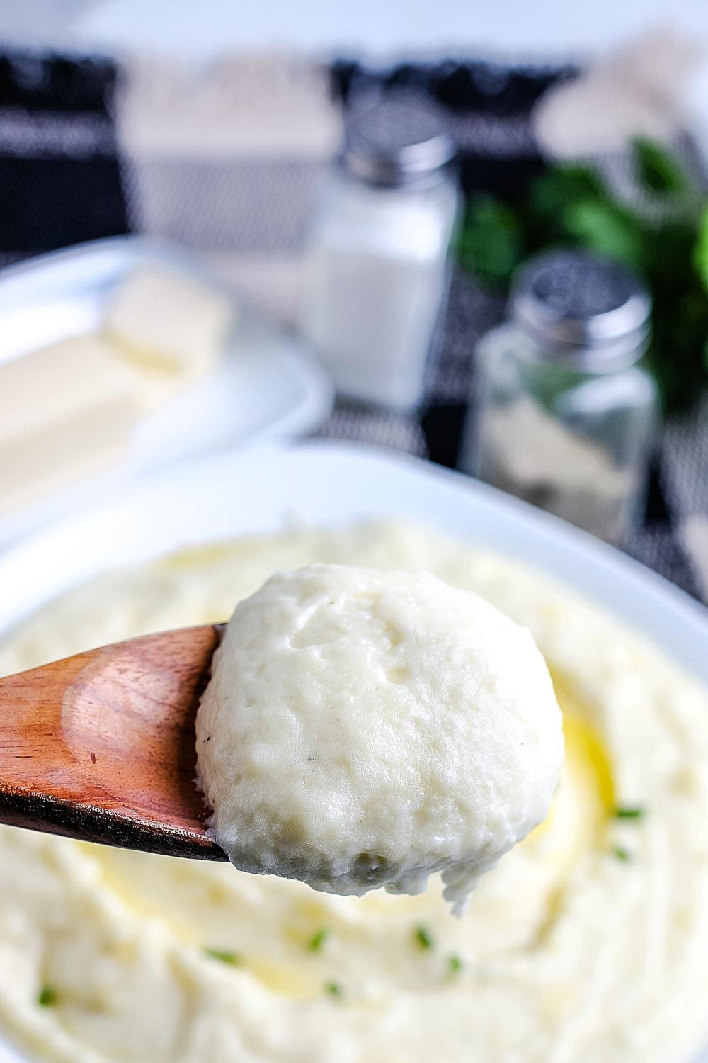A close up picture of a spoon picking up some mashed potatoes made with cream.