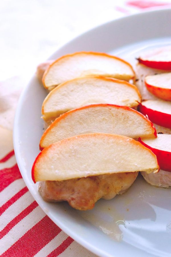 Overhead picture of baked pork chops with apples on a white plate.