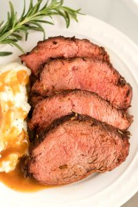 Beef roast on a plate with mashed potatoes and brown gravy.