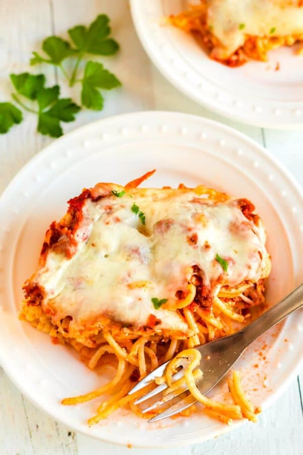 A slice of baked spaghetti on a white plate.