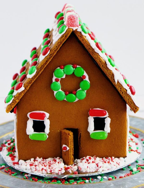 Gingerbread house decorated with red, green, and white candies.