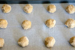 Roll dough balls in brown sugar and place on prepared baking sheet.