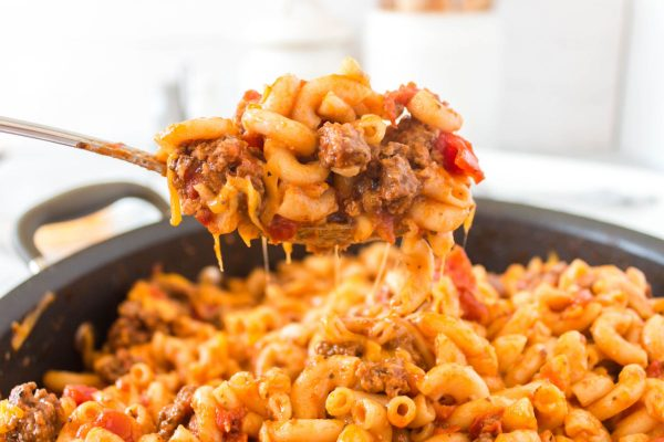 A spoon picking up a heap of American Goulash with cheese pulls trailing behind it.