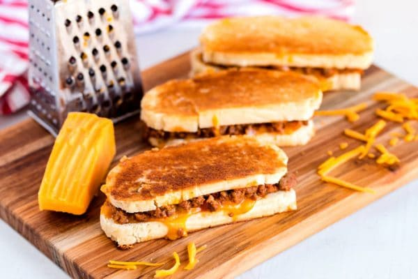 3 grilled cheese sandwiches on a wooden cutting board.