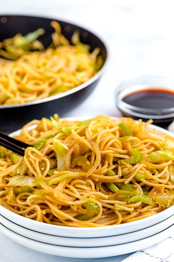 Chow Mein on a white plate with chopsticks.