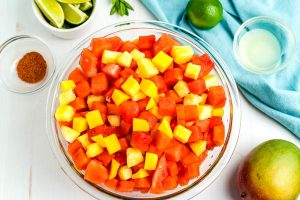 Place all of the fruit, except for the lime juice, in a large bowl.