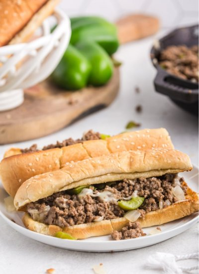 A sloppy joe on a white plate with more of the filling in the background.