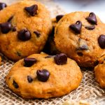 A close up picture of soft pumpkin chocolate chip cooked stacked together.