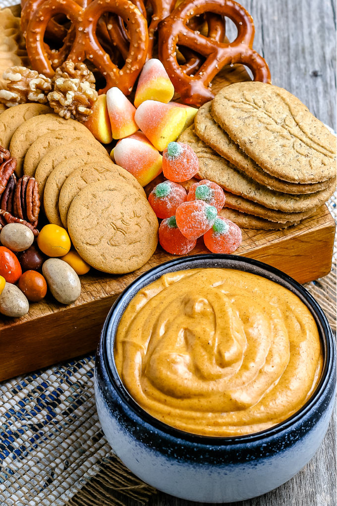 A blue bowl full of the pumpkin dip with candies, cookies, and pretzels in the background.