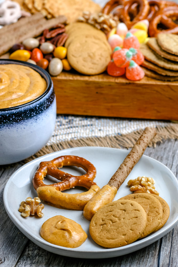 pretzels, cookies, and nuts on a white plate with some dip on the plate, too.