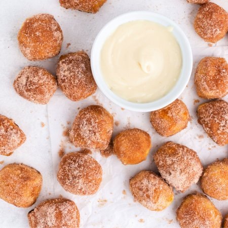 An up close picture copycat cinnamon sugar pretzel bites with a bowl full of cream cheese icing.