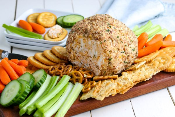The finished classic cheese ball on a wooden serving board.