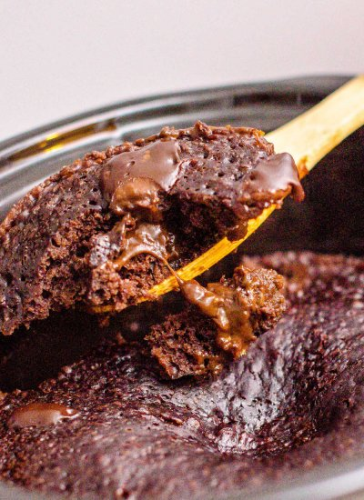 A serving spoon lifting up a scoop of chocolate lava cake.