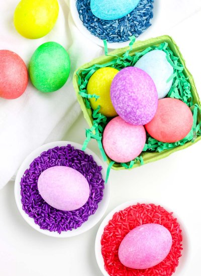 An overhead picture of dyed Easter eggs in a bowl and in dishes.