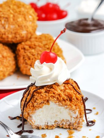 Fried Ice Cream on a white plate with a bite taken out of it.