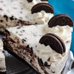 A slice of No Bake Oreo Cheesecake being taken out of the bigger cake.