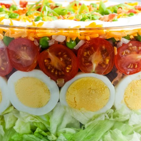 A close up picture of the finished seven layer salad in a clear glass serving bowl.