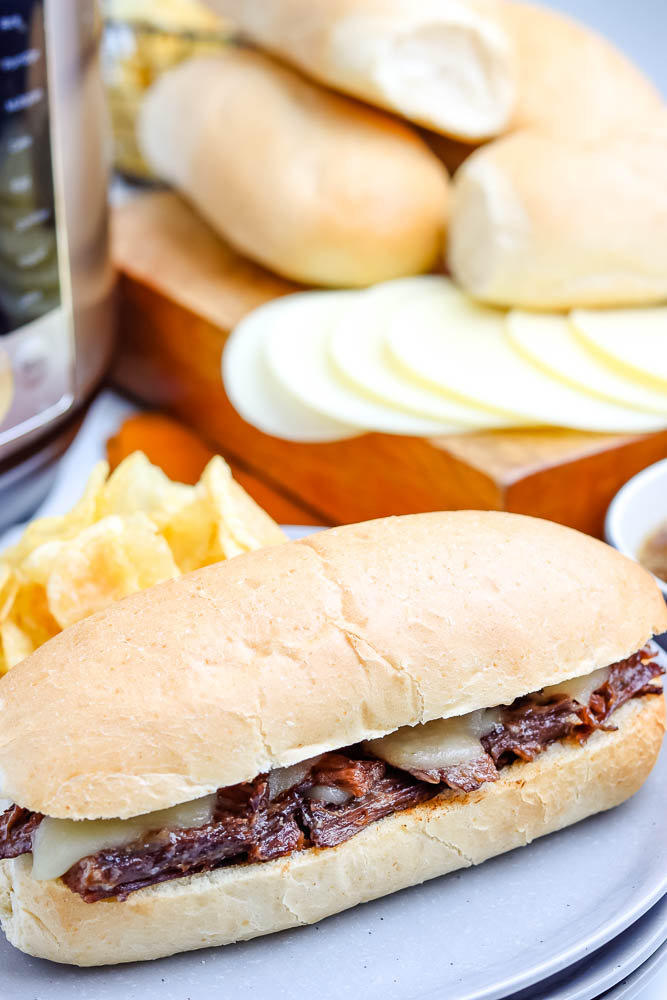 A French Dip Sandwich served on a hoagie roll and with potato chips.