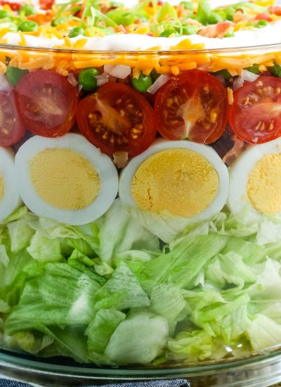 A close up picture of a 7 Layer Salad in a trifle serving dish.