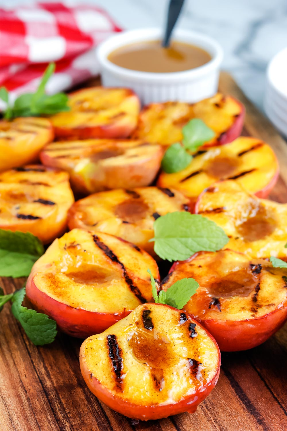 The finished Grilled Peaches on a wooden cutting board.