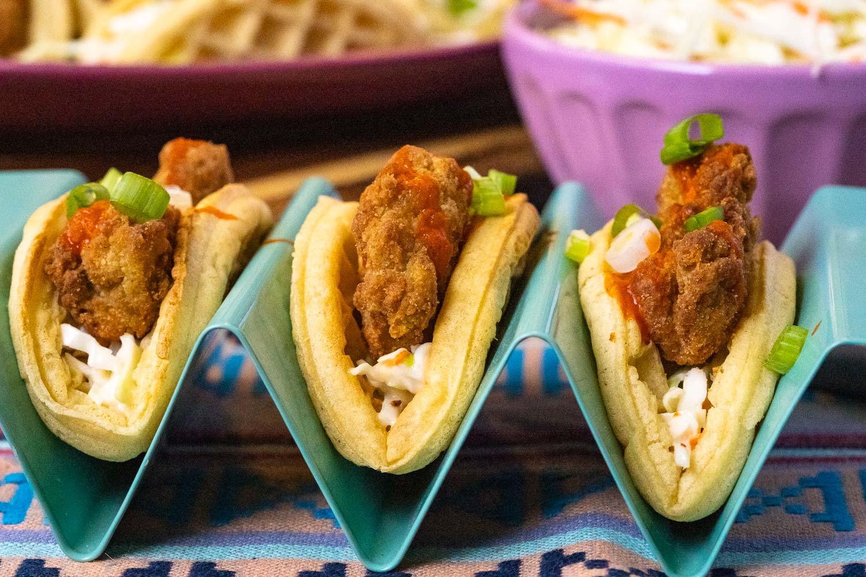 Three waffle tacos in a taco holder.