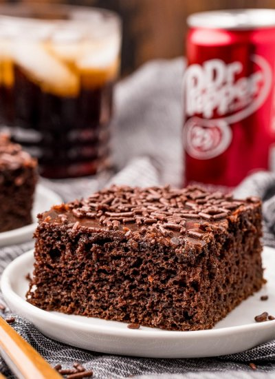 The finished Dr Pepper Cake slice on a white plate with a can of Dr Pepper in the background.