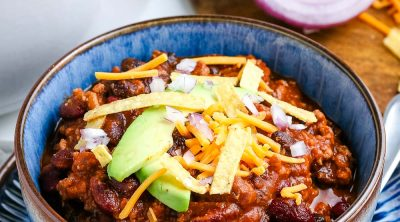 A bowl of Ground Turkey Chili with the white pot in the background.