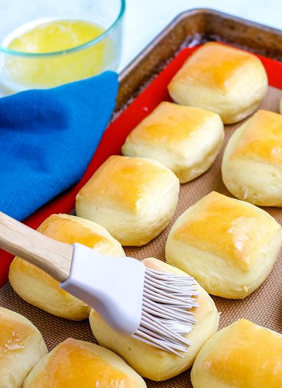 Butter being brushed on top of the finished rolls.