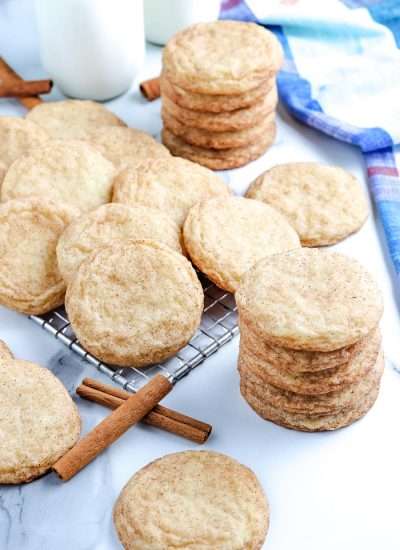 The finished Snickerdoodle Cookies stacked on top of each other and on a wire cooling rack.