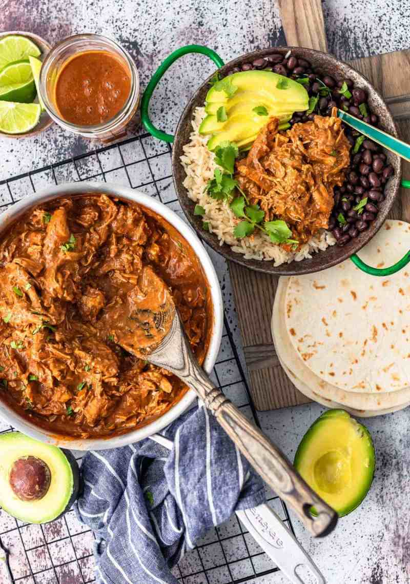 overhead picture of chicken mole in skillet plus plated with rice and black beans