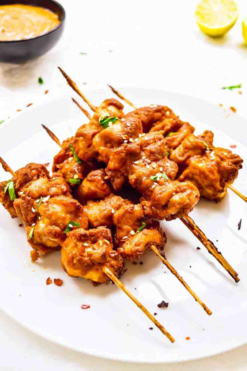 chicken satay skewers on a plate stacked
