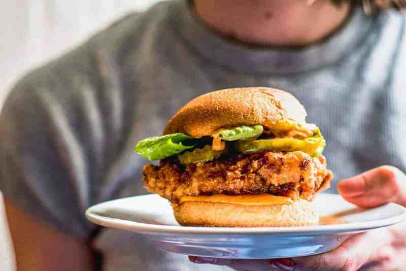 A plate with the best fried chicken sandwich on being held towards the camera