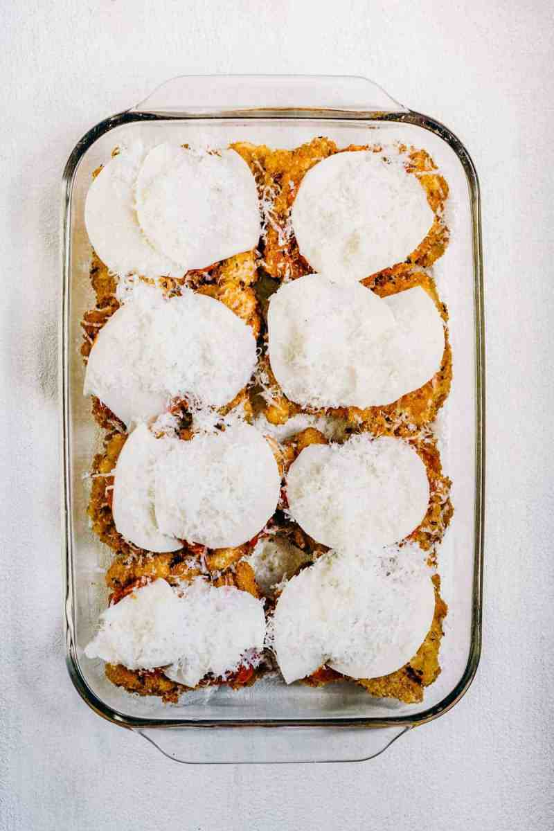 Chicken topped with cheese before being baked