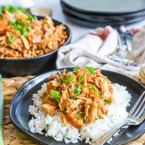 Plate of Crockpot Pineapple Chicken over Rice with a fork