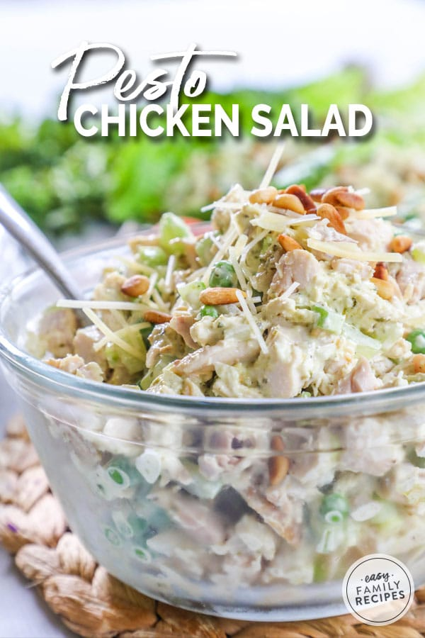 Pesto Chicken Salad served in a large glass bowl garnished with pine nuts and parmesan cheese