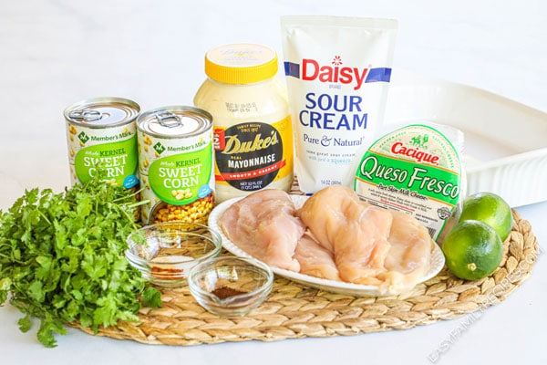 Ingredients to make Mexican Street Corn Chicken including chicken breast, mayo, sour cream, corn, cheese, lime, cilantro
