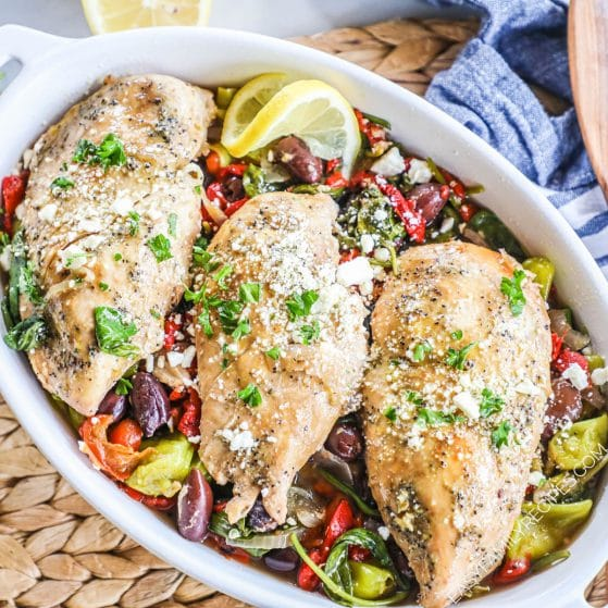 Serving dish with greek chicken with red onion, pepperoncini peppers, roasted red peppers, spinach and olives