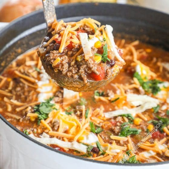Ladle serving ground beef enchilada soup with sour cream and cheese