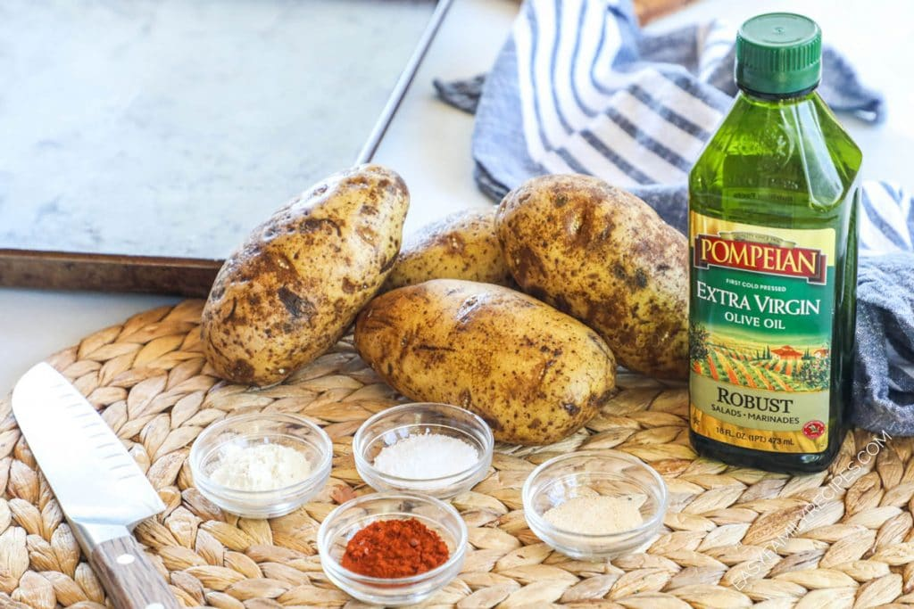 Ingredients for making baked potato wedges - potatoes, oil, salt, garlic powder, paprika, onion powder