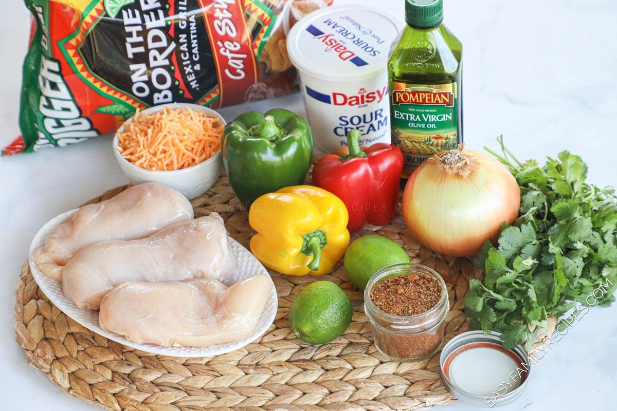 Chicken Fajita Nachos Ingredients including chicken breast, bell pepper, onion, chips, lime, cheese, sour cream