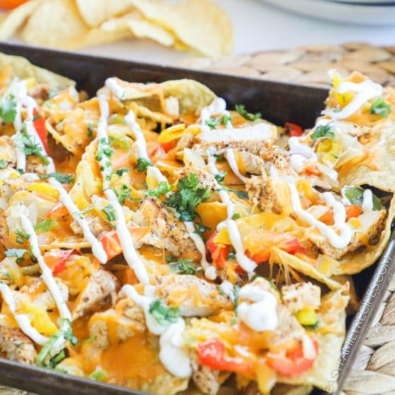 Cheesy Chicken Fajita Nachos baked on a sheet pan and drizzled with sour cream.