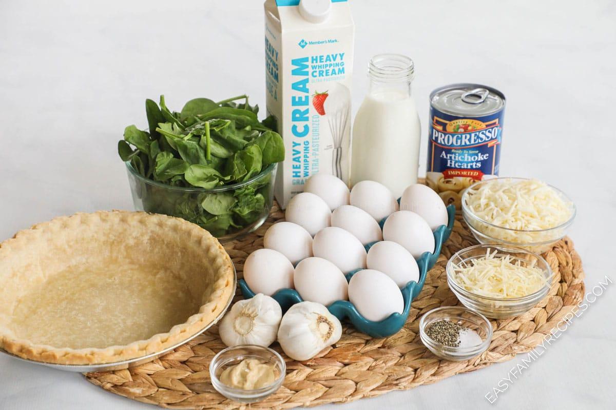 Ingredients for Spinach artichoke Quiche recipe including: pie crust, eggs, cream, fresh spinach, artichokes, cheese, mustard, salt and pepper