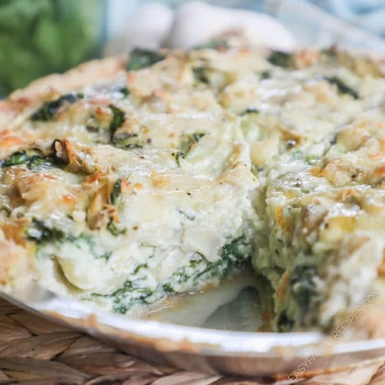 Slice cut out of Spinach Artichoke Quiche showing layers of spinach, artichokes and cheese in the egg custard.